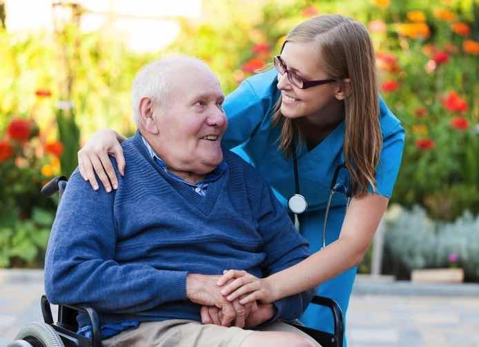 smilimg old man in wheelchair with friendly nurse
