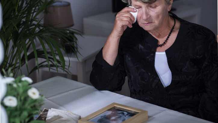 sad old woman looking at photo of deceased husband