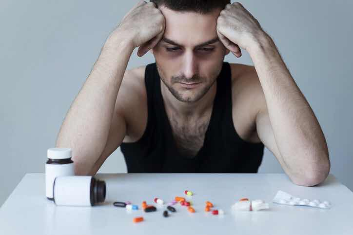 Man looking at pills spread on table