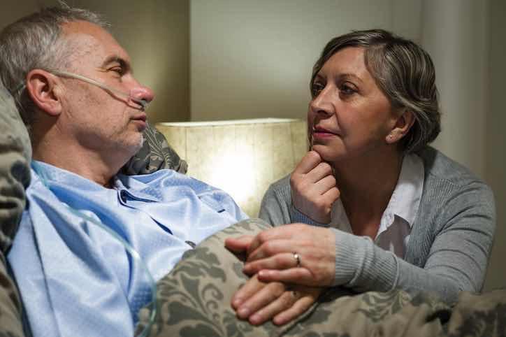 sad older woman sits by hospital bed of elderly man
