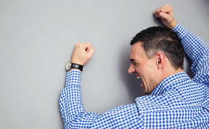 angry man pounding against wall