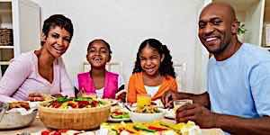 happy family seated at table eating healthy dinner