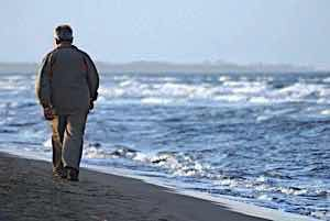 lonely sad older man walking alone by the shore