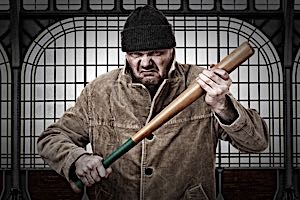 mean looking thug holding baseball bat threatiningly
