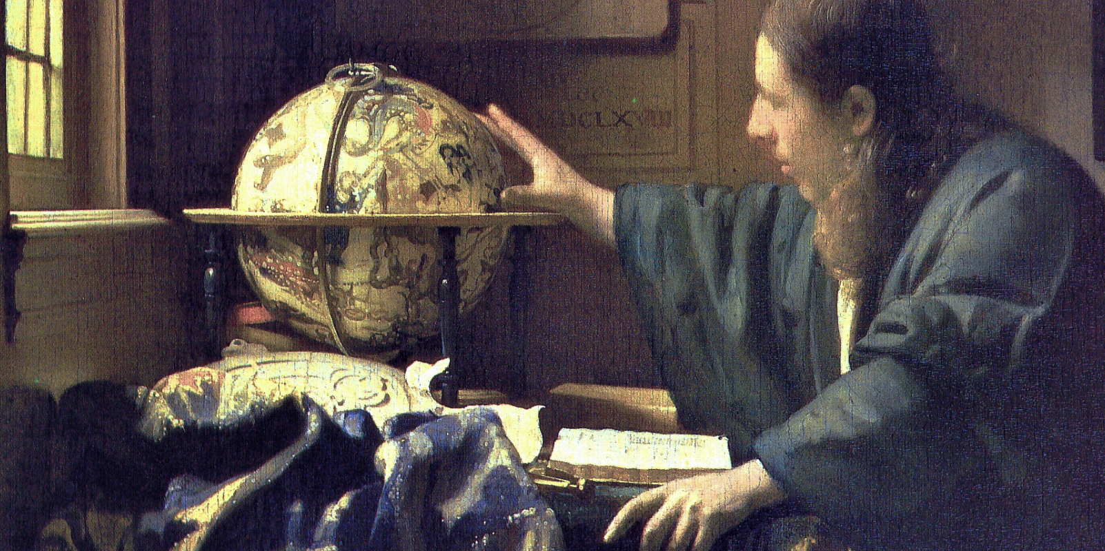 man looking at and touching a globe of the earth