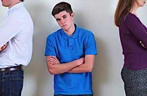 angry teen boy with arms folded with parents