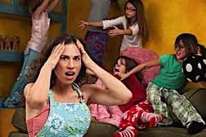 Upset angry frustrated mother with hands on head among mischievous little girls