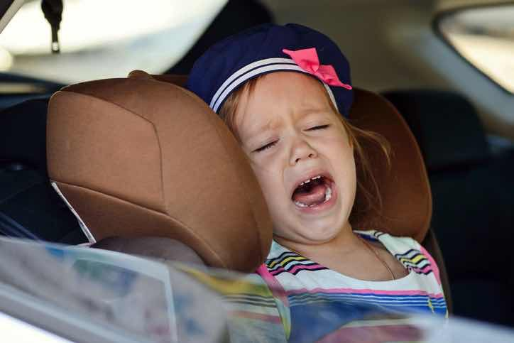 angry toddler girl in car seat