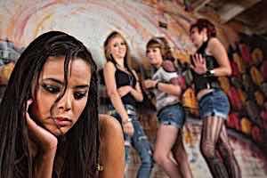 three teenage girls laughing at sad teenage girl