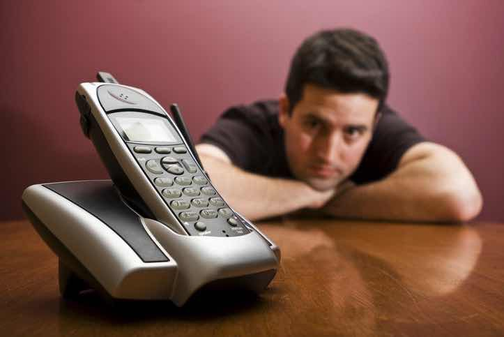 man waits anxiously by a cell phone