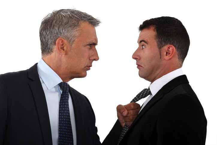 angry businessman  threatens scared businessman