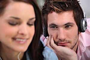 man wearing headphones gazing admiringly at smiling woman