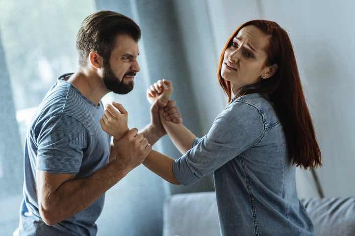 Man angry and losing temper and holding a woman\\\'s arms