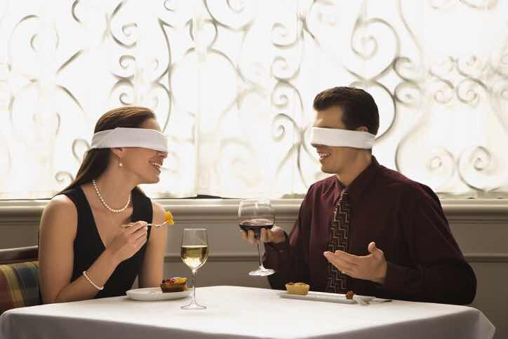 blindfolded man and woman on a dinner date